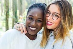 Olik stående av två attraktiva tonåriga flickvänner utomhus Royaltyfri Foto