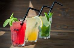 Olik uppfriskande lemonad tre med citronen och limefrukt på en träbakgrund för citrus vatten för sommar drinkis för karaff orange Arkivfoto