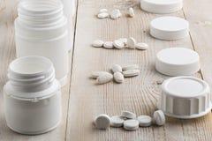 Olik vit plast- preventivpillerflaskor och hög av droger Royaltyfri Foto