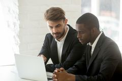 Olika affärsmän i dräkter som tillsammans analyserar online-nolla för projekt arkivfoto
