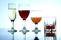 Olika alkoholdrycker i exponeringsglas och bägare Arkivfoto