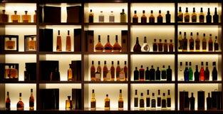 Olika alkoholflaskor i en stång, tillbaka ljus, logoer som tas bort Royaltyfri Fotografi