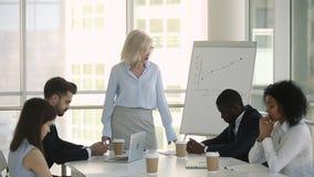 Olika anställda som sitter på tabellen som grälas på av det irriterade kvinnliga framstickandet arkivfilmer