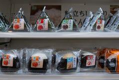 Olika anstrykningar av den japanska risonigirien som säljs på konbinien för uttag för familjmarknadbekvämlighet i Osaka, Japan arkivbild