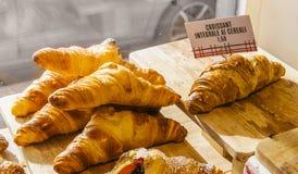 Olika anstrykningar av gifflet eller som i Italien deras kallade brioche på skärm i ett bageri i Milan, Italien med ett pris och  arkivfoton