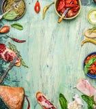 Olika antipasti med ciabattabröd, pesto och skinka på lantlig träbakgrund, bästa sikt, ram Royaltyfri Fotografi