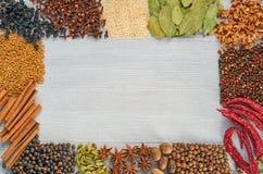 Olika aromatiska indierkryddor och örter på det gråa köksbordet Kryddatexturbakgrund med kopieringsutrymme arkivbild