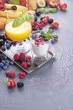 Olika bär och frukter på en grå bakgrund, fruktsaft från nya frukter, yoghurt och bär för frukostvitaminer och detox royaltyfri bild