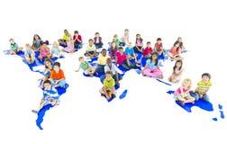 Olika barn som sitter på världskarta Royaltyfri Foto