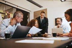 Olika businesspeople på arbete tillsammans i en kontorsstyrelse arkivfoto