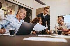 Olika businesspeople som har ett möte i en kontorsstyrelse royaltyfri bild