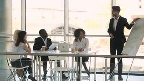 Olika businesspeople som sitter på den lyssnande affärslagledaren för tabell under utbildning arkivfilmer