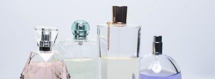 Olika doftflaskor på vit bakgrund Parfymeriaffär skönhetsmedel Baner för website Arkivfoton