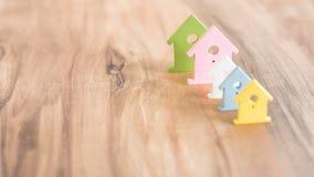 Olika färgade hussymboler som blir i en linje på brun träyttersida Royaltyfri Foto