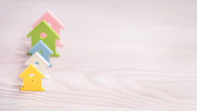 Olika färgade hussymboler som blir i en linje på ljus träyttersida Royaltyfri Bild