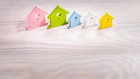 Olika färgade hussymboler som blir i linje på ljus träyttersida Royaltyfri Bild
