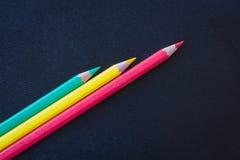 Olika färgblyertspennor som vässas på mörk bakgrund Arkivbild