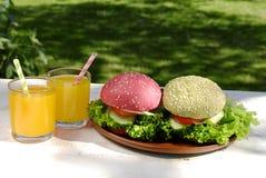 Olika färger av hamburgare och orange fruktsaft Arkivbild