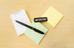 Olika färger av postiten med viktigt ord och den svarta pennan på Royaltyfri Fotografi