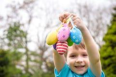 Olika färgpåskägg i ett ägg för händer för barn` s jagar Arkivbilder