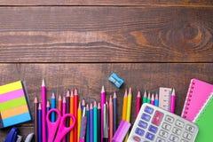 Olika färgrika skola- och kontorstillförsel på en brun trätabell royaltyfria foton