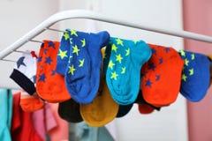 Olika färgrika sockor på att torka kuggen mot suddig bakgrund arkivbilder