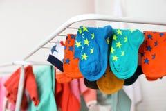 Olika färgrika sockor på att torka kuggen mot suddig bakgrund royaltyfri fotografi