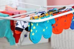Olika färgrika sockor på att torka kuggen mot suddig bakgrund arkivfoto