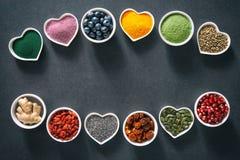 Olika färgrika superfoods i bunkar på mörk bakgrund arkivbild