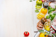 Olika färgrika tomater med flaskan av olja- och salladättiksås, basilika och kryddor på vit träbakgrund, bästa sikt royaltyfri fotografi