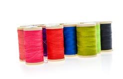 Olika färgsömnadtrådar på en rulle Arkivbild