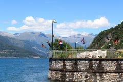 Olika flaggor på byn Varenna på sjön Como med berg i Lombardy Royaltyfri Fotografi