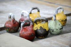 Olika format av kettlebells väger att ligga på idrottshallgolv utrusta arkivbild