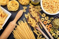 Olika former av rå pasta på svart bakgrund Fotografering för Bildbyråer