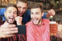 Olika fotbollsfan som h?ller ?gonen p? fotboll p? smartphonen och firar segerst?llningen i bar royaltyfria bilder