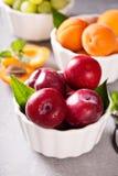 Olika frukter i vita bunkar Arkivfoton