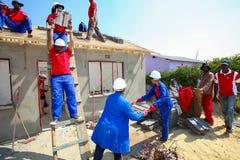 Olika gemenskapmedlemmar som bygger ett low costhus i Soweto Arkivfoton
