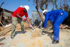 Olika gemenskapmedlemmar som bygger ett low costhus i Soweto Arkivfoto