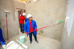 Olika gemenskapmedlemmar som bygger ett low costhus i Soweto Royaltyfri Bild