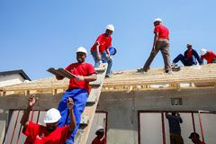 Olika gemenskapmedlemmar som bygger ett low costhus i Soweto Fotografering för Bildbyråer