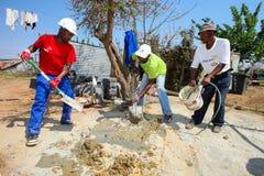 Olika gemenskapmedlemmar som bygger ett low costhus i Soweto Royaltyfria Foton