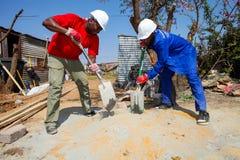 Olika gemenskapmedlemmar som bygger ett low costhus i Soweto Royaltyfri Fotografi
