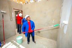 Olika gemenskapmedlemmar som bygger ett low costhus i Soweto Royaltyfria Bilder