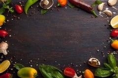 Olika grönsaker och örter på den mörka wood tabellen Royaltyfri Bild