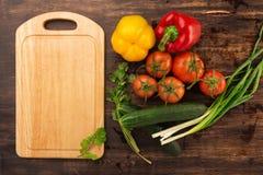 Olika grönsaker och tom skärbräda Arkivfoto