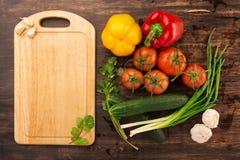 Olika grönsaker och tom skärbräda Arkivfoton