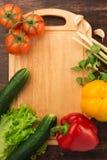 Olika grönsaker och tom skärbräda Royaltyfria Foton