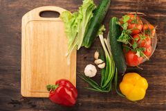 Olika grönsaker och tom skärbräda Royaltyfri Bild