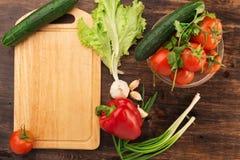 Olika grönsaker och tom skärbräda Royaltyfri Foto