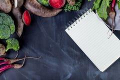 Olika grönsaker på svart med anteckningsboken Fotografering för Bildbyråer